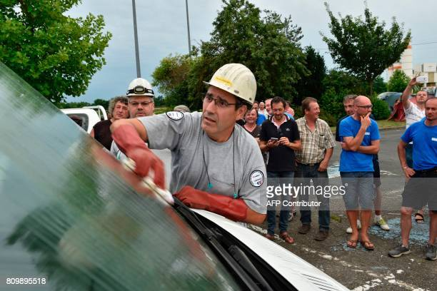 An employee of PSA automotive group attempts to clean a van that got dirty by demonstrating unionists during a blockade to access the the SeptFons...