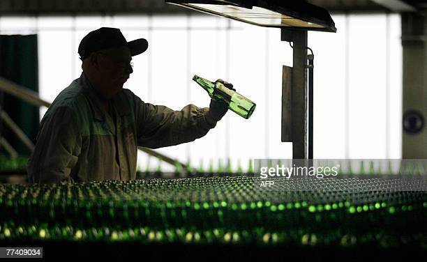An employee of SaintGobain Oberland controls 17 October 2007 a glass bottle at their glass production site in Wirges western Germany where some 10...
