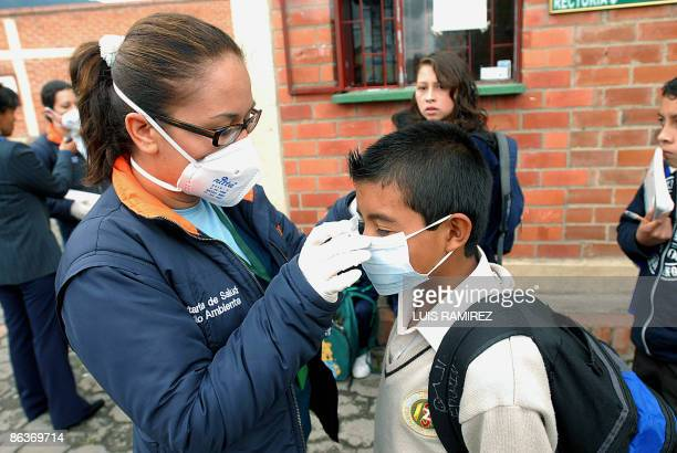 An employee of Social Protection explains to a schoolboy how to put the face mask on at school on May 4 2009 in Zipaquira Cundinamarca Department...