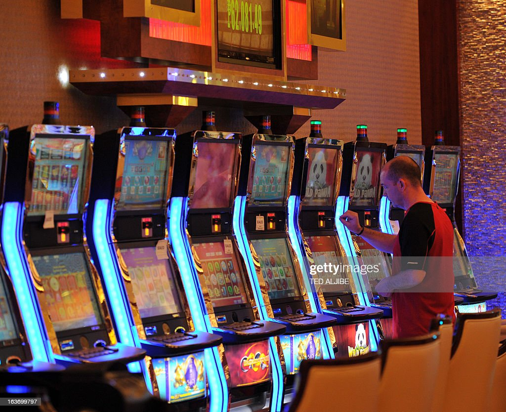An employee of Solaire Resorts and casino, checks gaming paraphaernalia during a dry run at the casino in Manila on March 14, 2013, ahead of its opening on March 16. The Philippines makes its biggest bet this weekend in a high-stakes bid to join the world's elite gaming destinations, with the launch of a $1.2-billion casino on Manila Bay.Solaire Manila Resorts is the first of four enormous entertainment venues slated to rise over a giant chunk of prime, reclaimed land that industry and government leaders expect will attract millions of cashed-up Asian tourists.