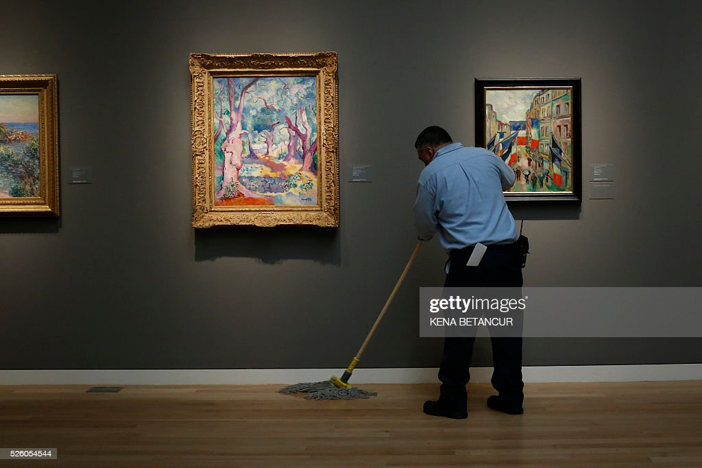 An employee of Sotheby's cleans the floor of the 10th floor galleries on April 29, 2016 during a press preview of Sotheby's forthcoming evening auctions of Impressionist, Modern Art and Contemporary Art that will take place May 9 and 11, in New York. / AFP / KENA