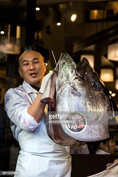 An employee of sushi restaurant chain SushiZanmai holds the head of a 212kilogram bluefin tuna after cutting it up at the restaurant near the Tsukiji...