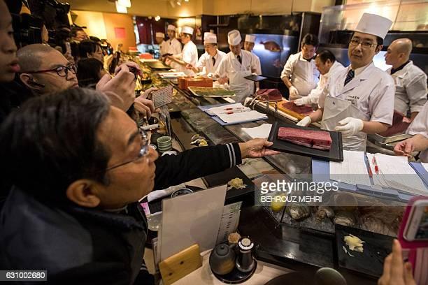 An employee of sushi restaurant chain SushiZanmai shows a cut of a 212kilogram bluefin tuna to a customer at their restaurant near the Tsukiji fish...
