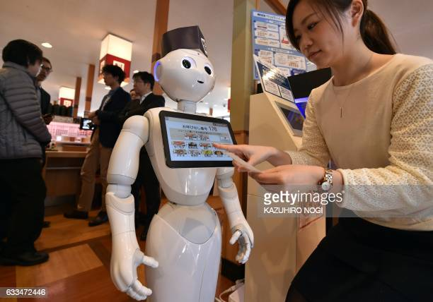 An employee of sushi restaurant Hamazushi looks at a touch screen set up on Japanese telecom giant Softbank's humanoid robot Pepper during a press...