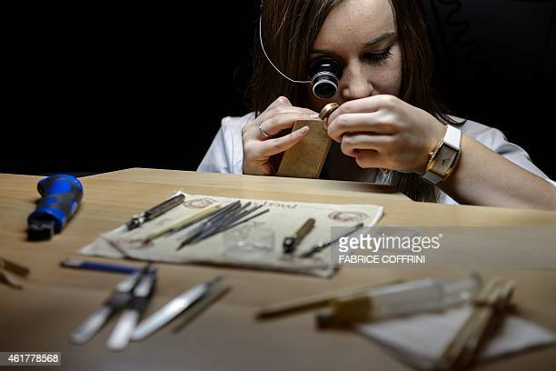 An employee of Swiss watchmaker Piaget owned by Richemont the world's secondlargest luxury goods firm assembles a wristwatch on January 19 2015 at...