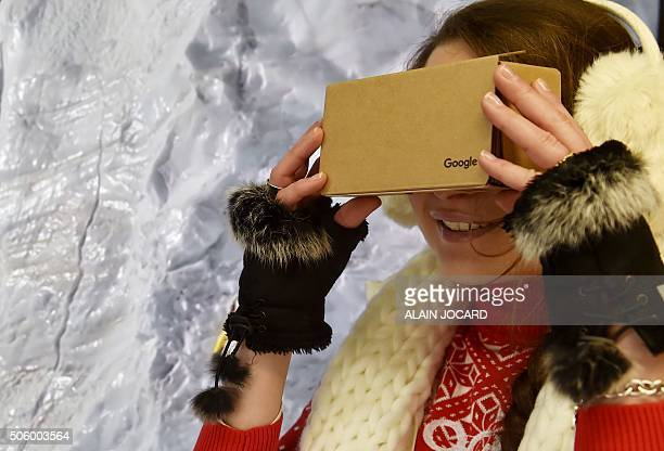 An employee of Tech giant Google dons a Google 'Virtual Reality' headset as she poses for photographs during the opening an event in Paris on January...