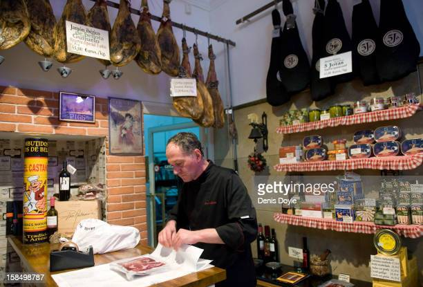 An employee of the Alberto Lopez Araque jamon shop in Madrid wraps a selection of drycured Jamon Iberico de bellota on December 14 2012 in Madrid...
