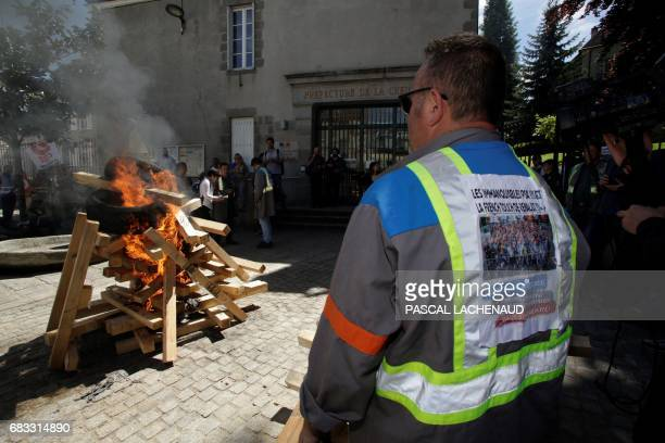 An employee of the automotive supplier Industry in La Souterraine stands in front of burning wood outside the prefecture of Gueret on May 15 2017...