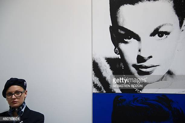 An employee of the Basel Art fair stands next to a work of art by US artist Andy Warhol on June 17 2014 during the preview day of the Art Basel fair...