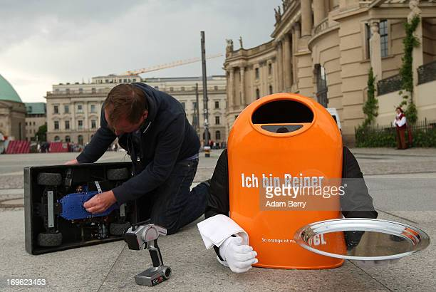 An employee of the Berliner Stadtreinigungsbetriebe city garbage removal company tries to repair a broken trash canshaped robotic butler named Reiner...