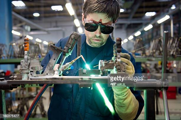 An employee of the bicycle company Brompton works on components for the folding bicycles on the production line at the company's headquarters in west...
