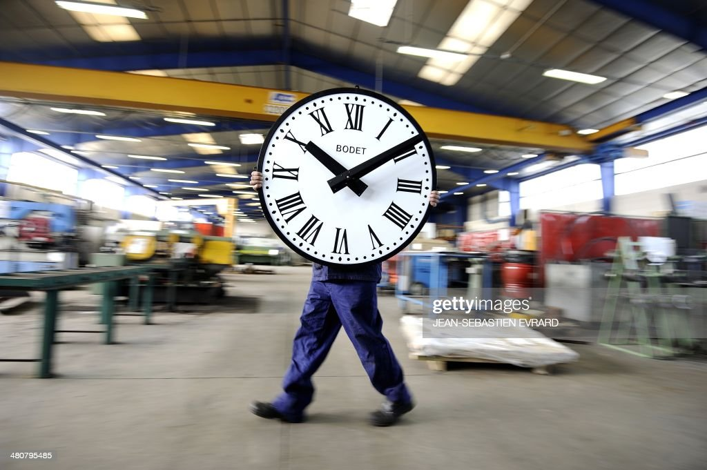 An employee of the Bodet Company carries a clock on March 26, 2014 at the plant of Trementines, western France. The Bodet company manufactures clocks since 1868 for churches, stations, sports halls and employs 630 workers in France. AFP PHOTO / JEAN-SEBASTIEN EVRARD