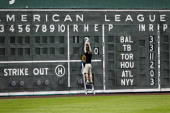 An employee of the Boston Red Sox updates the scoreboard during a Grapefruit League Spring Training Game against the Pittsburgh Pirates at JetBlue...