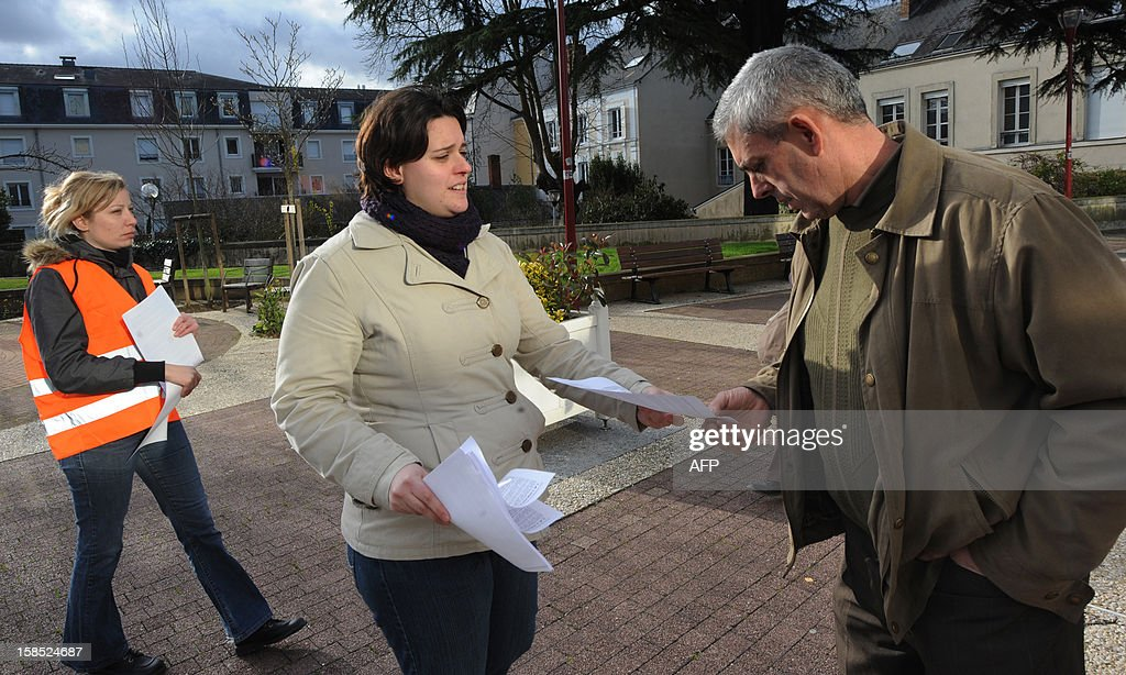 An employee (C) of the Candia milk packaging site distributes leaflets to a farmer, on December 18, 2012 in Le Mans, in western France, before an information meeting organised by its owner the Sodiaal cooperative group. The group decided to close three plants in France involving the loss of 313 jobs, including 192 in the factory of Lude, western France.