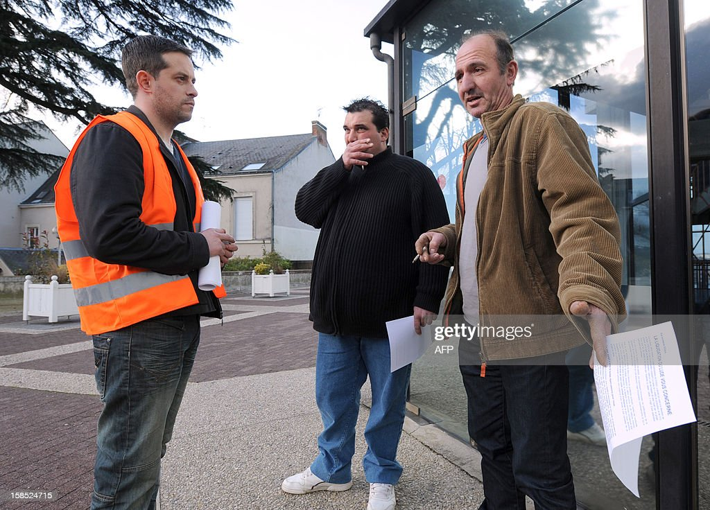 An employee (L) of the Candia milk packaging site speaks with farmers, on December 18, 2012 in Le Mans, in western France, before an information meeting organised by its owner the Sodiaal cooperative group. The group decided to close three plants in France involving the loss of 313 jobs, including 192 in the factory of Lude, western France.