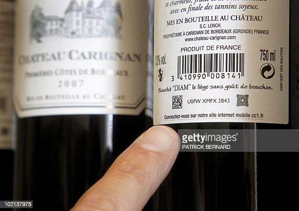 'UN TATOUAGE NUMERIQUE POUR SUIVRE A LA TRACE SA BOUTEILLE DE BORDEAUX' An employee of the Chateau Carignan wine indicates a numeric marker included...