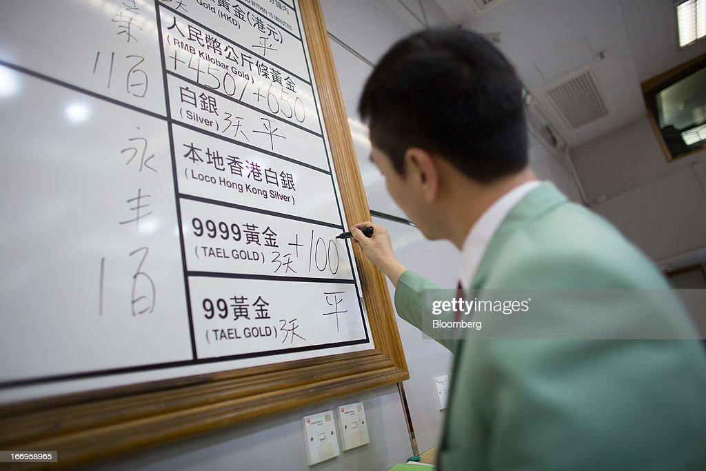 An employee of The Chinese Gold and Silver Exchange Society writes down prices of gold on the board in the trading hall of The Chinese Gold and Silver Exchange Society in Hong Kong, China, on Friday, April 19, 2013. Gold traders are divided on whether bullion will extend declines after the biggest plunge in three decades generated buying from investors and jewelers. Photographer: Lam Yik Fei/Bloomberg via Getty Images