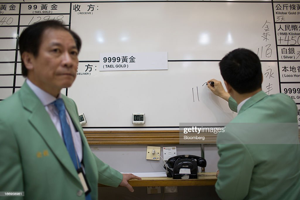 An employee of The Chinese Gold and Silver Exchange Society writes the price of '999.9 Tael' gold on the board while his colleague looks on in the trading hall of The Chinese Gold and Silver Exchange Society in Hong Kong, China, on Friday, April 19, 2013. Gold traders are divided on whether bullion will extend declines after the biggest plunge in three decades generated buying from investors and jewelers. Photographer: Lam Yik Fei/Bloomberg via Getty Images