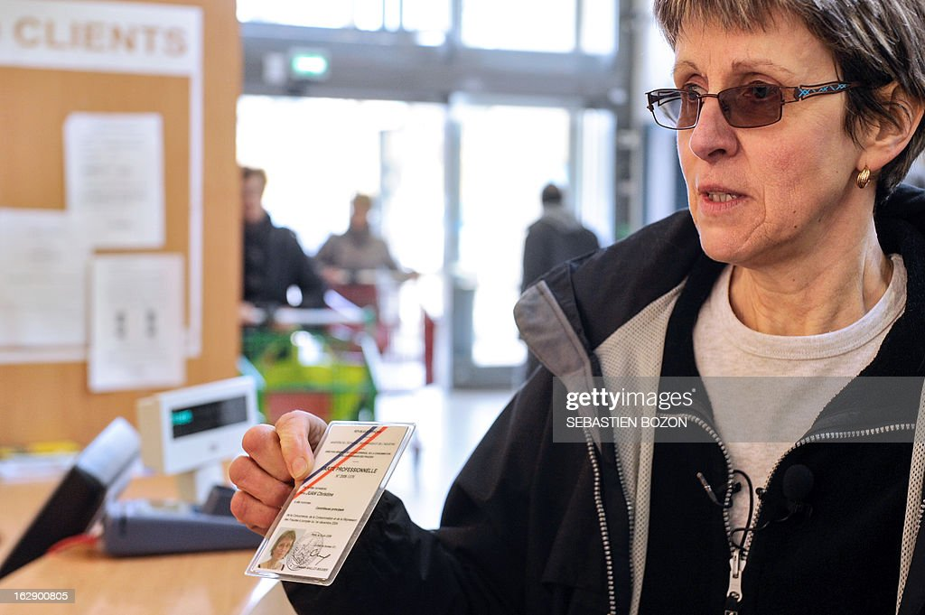 An employee of the DDCSPP (Departmental Directorate of Social Cohesion and Protection of Populations) shows her official card before conducting a verification of the origine of the meat in a supermarket in Besançon, eastern France, on March 1, 2013. An Europe-wide food fraud scandal over horsemeat sold as beef emerged in mid-January when Irish authorities found traces of horse in beefburgers made by firms in Ireland and Britain and sold in supermarket chains including Tesco and Aldi. The scandal intensified earlier this month when Comigel -- a French frozen meal maker which bought 500 tonnes of mislabelled horsemeat from Spanghero -- alerted Findus to the presence of horsemeat in the meals it had made for the food giant and which were on sale in Britain. AFP PHOTO / SEBASTIEN BOZON