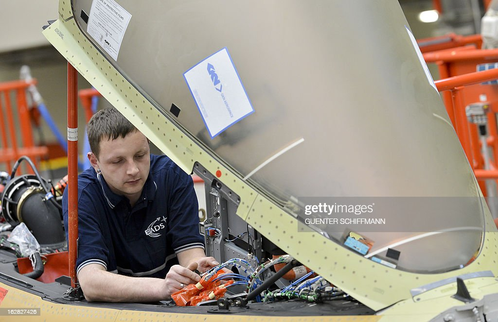An employee of the EADS company Cassidian sits in the cockpit as he works on the assembling of an Eurofighter plane for the German Air Force at the Cassidian production line in Manching, southern Germany, on February 28, 2013.