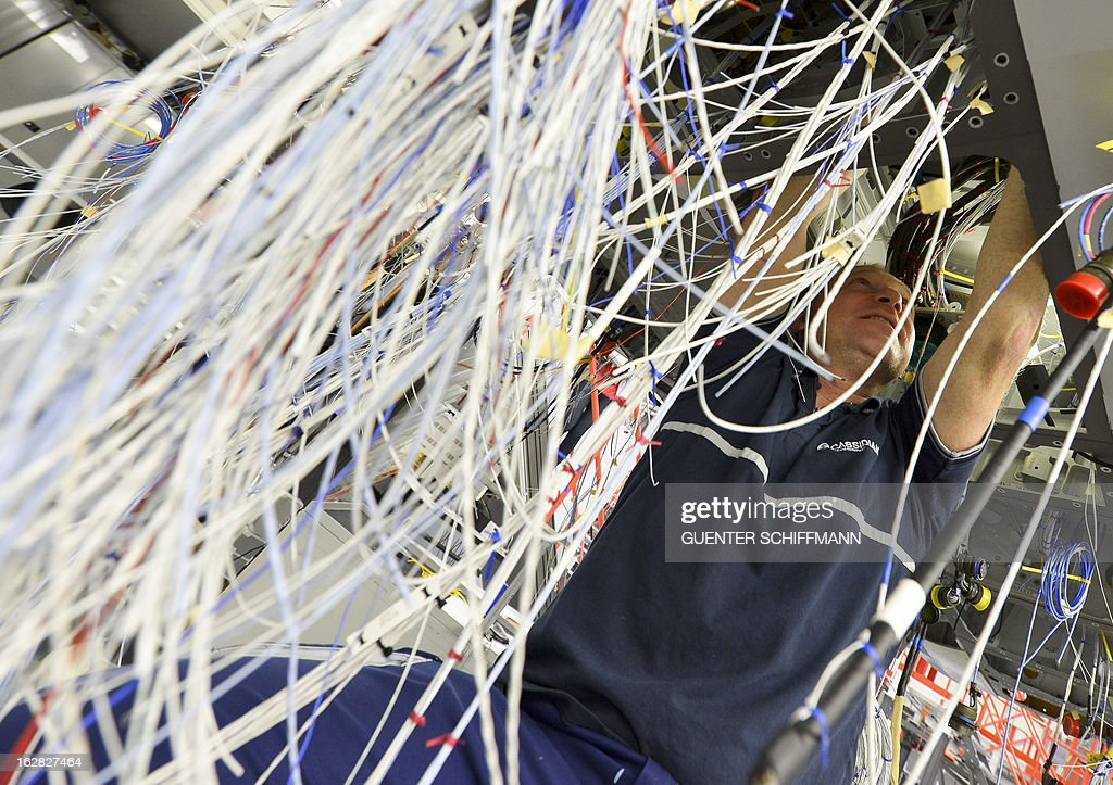 An employee of the EADS company Cassidian works on the cabling at the center fuselage as he assembles an Eurofighter plane for the German Air Force at the Cassidian production line in Manching, southern Germany, on February 28, 2013.