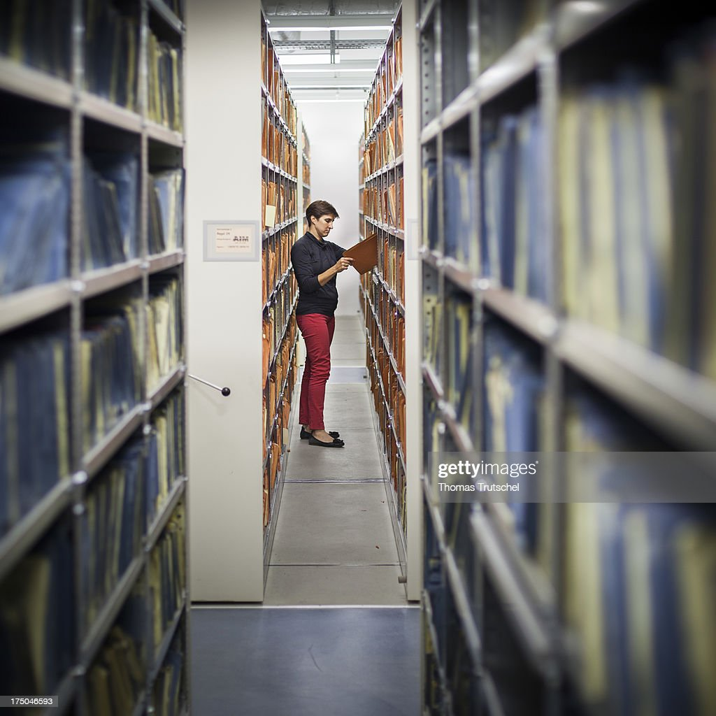 An employee of the federal archive views documents in the federal archive of the former East German secret police, known as the Stasi, on July 30, 2013 in Berlin, Germany. The agency of the Federal Commissioner for the Stasi records (BStU), manages the archives of the former East German secret police 'Stasi'. It preserves and protects the records of The Ministry for State Security of the former German Democratic Republic (GDR), making them available to private citizens, institutions and the public in accordance with strict legal regulations. The Stasi, whose official function was to protect the East German communist party, pursued an extremely aggressive campaign of spying on East German citizens in order to confine and root out dissent. The archive contains information gathered by the Stasi on millions of people.
