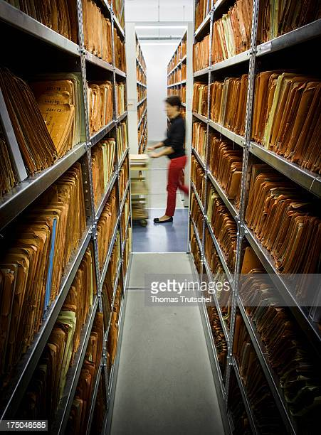 An employee of the federal archive walks past documents in the federal archive of the former East German secret police known as the Stasi on July 30...