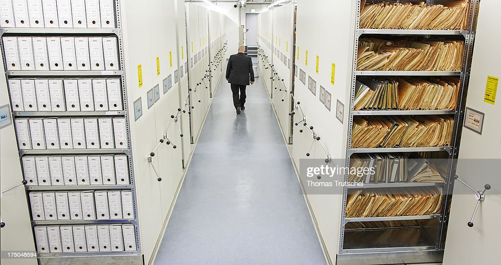 An employee of the federal archive walks past documents in the federal archive of the former East German secret police, known as the Stasi, on July 30, 2013 in Berlin, Germany. The agency of the Federal Commissioner for the Stasi records (BStU), manages the archives of the former East German secret police 'Stasi'. It preserves and protects the records of The Ministry for State Security of the former German Democratic Republic (GDR), making them available to private citizens, institutions and the public in accordance with strict legal regulations. The Stasi, whose official function was to protect the East German communist party, pursued an extremely aggressive campaign of spying on East German citizens in order to confine and root out dissent. The archive contains information gathered by the Stasi on millions of people.
