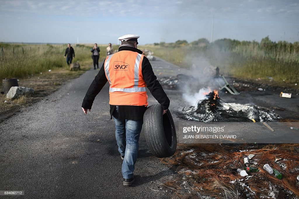 An employee of the France's national state-owned railway company (SNCF) holds a tire to burn it as striking workers block the access to an oil depot near the Total refinery of Donges, western France, on May 25, 2016 to protest against the government's planned labour law reforms. France has been using strategic fuel reserves for two days in the face of widespread blockades of oil depots by union activists, the head of the oil industry federation said on May 25, 2016. / AFP / JEAN