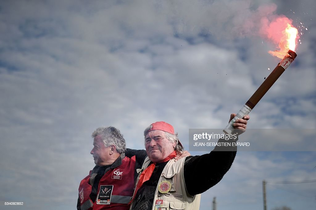 An employee of the France's national state-owned railway company (SNCF) raises a flare as they block the access to an oil depot near the Total refinery of Donges, western France, on May 25, 2016 to protest against the government's planned labour law reforms. France has been using strategic fuel reserves for two days in the face of widespread blockades of oil depots by union activists, the head of the oil industry federation said on May 25, 2016. / AFP / JEAN