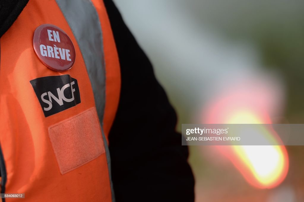 An employee of the France's national state-owned railway company (SNCF) wears a pin reading 'on strike' as they block the access to an oil depot near the Total refinery of Donges, western France, on May 25, 2016 to protest against the government's planned labour law reforms. France has been using strategic fuel reserves for two days in the face of widespread blockades of oil depots by union activists, the head of the oil industry federation said on May 25, 2016. / AFP / JEAN
