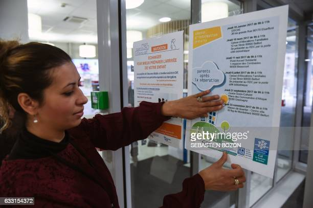 An employee of the France's Office for Family Allocations hangs a poster informing people about meetings for parents to assist in the restructuring...