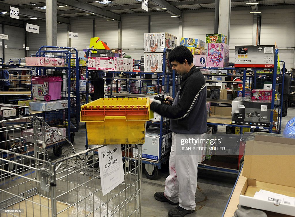 An employee of the French 'C Discount' online trade company checks barcodes as he prepares items in a store in Cestas, southwestern France, on December 14, 2012. AFP PHOTO JEAN-PIERRE MULLER