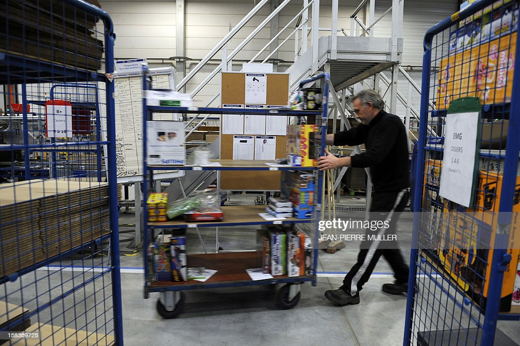 An employee of the French 'C Discount' online trade company pulls a trolley as he prepares items in a store in Cestas, southwestern France, on December 14, 2012.