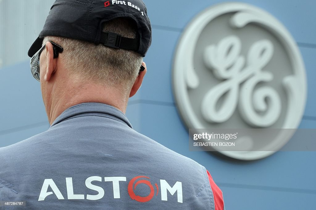 An employee of the French engineering group Alstom stands in front of the logo of the US company General Electric (GE) on April 29, 2014 in Belfort. The battle for Alstom was set to intensify Tuesday, with Siemens ready to confirm its bid for the French engineering group also coveted by US rival General Electric, an informed source said. French President Francois Hollande vowed on April 28, 2014 to safeguard jobs at Alstom as he met with both GE and Siemens chiefs, while Germany sought to boost Siemens' case, saying a tie-up offered a 'big opportunity' for Europe's two largest economies. AFP PHOTO / SEBASTIEN BOZON