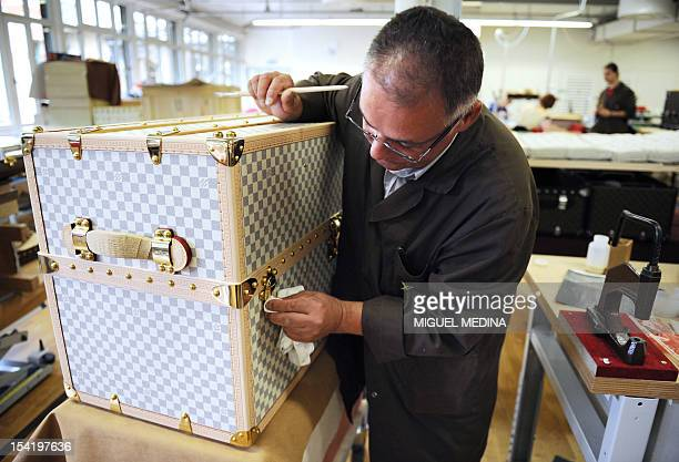 An employee of the French handbags compagny Louis Vuitton part of world's biggest luxury group LVMH cleans the lock of a trunk at the factory in...