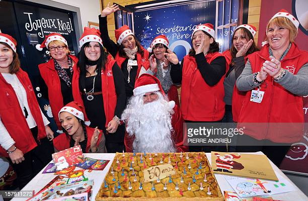 An employee of the French postal services La Poste dressed as Santa Claus poses next to others people employed to answer children letters to Santa...