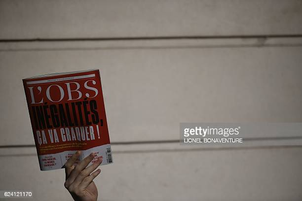 An employee of the French weekly news magazine 'L'Obs' holds a magazine reading 'Inequalities it will break down' as he demonstrates against the...