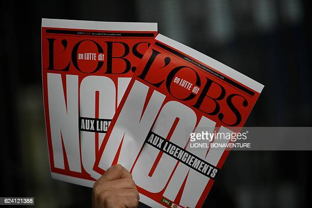 An employee of the French weekly news magazine 'L'Obs' holds banners reading 'Inequalities it will break down' as he demonstrates against the layoffs...