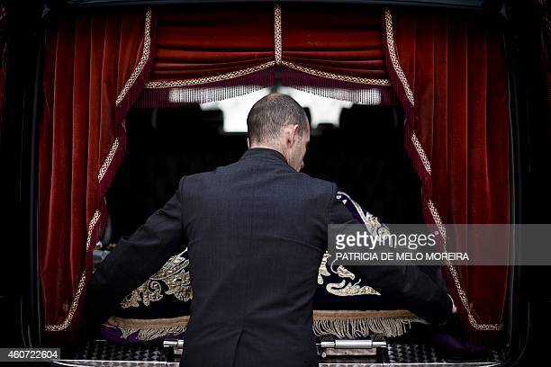 An employee of the funeral agency Servilusa pulls the coffin of an unclaimed body out of a hearse at Benfica cemetery in Lisbon on December 12 2014...