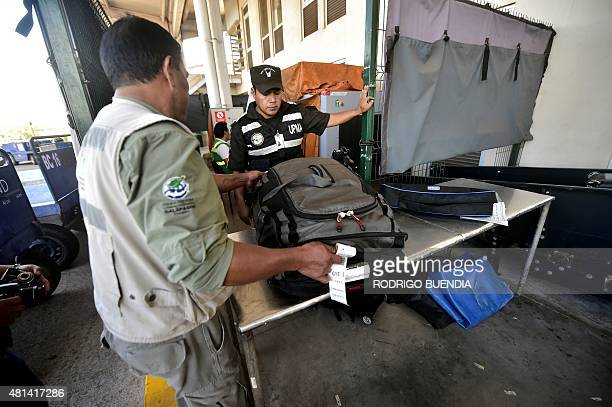An employee of the Galapagos National Park helps with the inspection of luggage at the airport in Baltra one of the 13 islands that make up the...