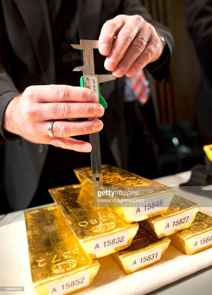 An employee of the German Federal Bank measures a bar of gold during a press conference at the German Federal Bank in Frankfurt am Main, western Germany, on January 16, 2013.The German central Bundesbank said it will relocate parts of its gold stored abroad following recent accusations that it is not keeping proper track of its vast reserves.