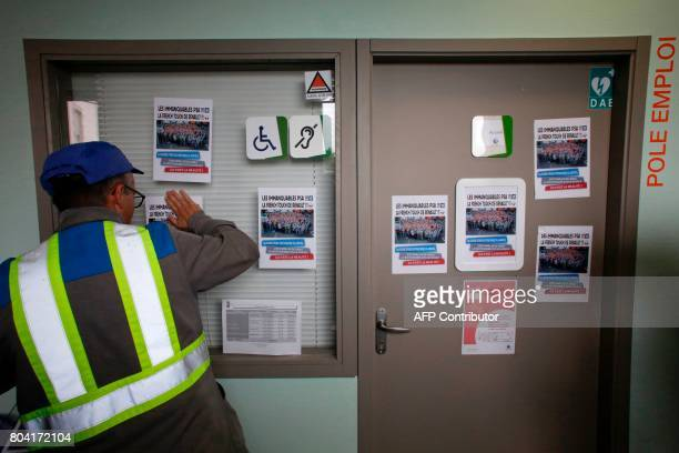 An employee of the GMS La Souterraine factory posts papers onto an employment office entrance on June 30 2017 in La Souterraine After months of...