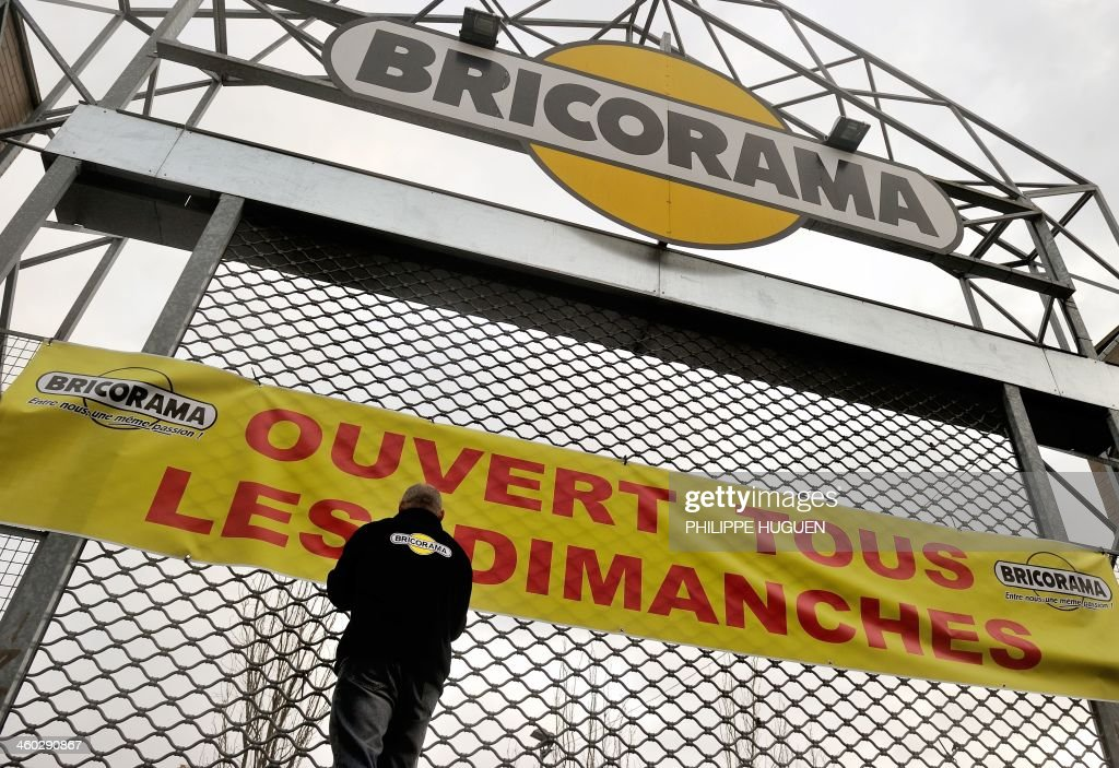 An employee of the home improvement chain Bricorama places a banner reading 'Open on all Sundays' on the gate of a branch in Lille on January 3, 2014. Home improvement stores will be allowed to open on Sundays under certain conditions after a fierce debate over the country's strict laws on trading on the traditional day of rest. AFP PHOTO/PHILIPPE HUGUEN