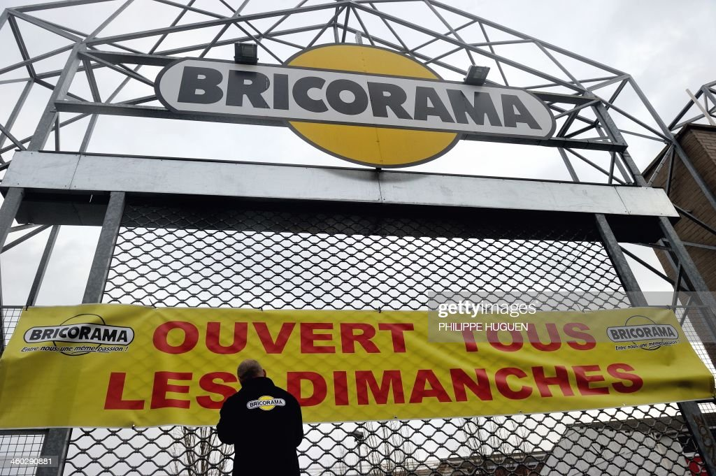 An employee of the home improvement chain Bricorama places a banner reading 'Open on all Sundays' on the gate of a branch in Lille on January 3, 2014. Home improvement stores will be allowed to open on Sundays under certain conditions after a fierce debate over the country's strict laws on trading on the traditional day of rest.