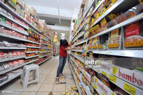 An employee of the Indonesia subsidiary of French supermarket chain Carrefour stocks shelves at one of the company's supermarkets in Jakarta on...