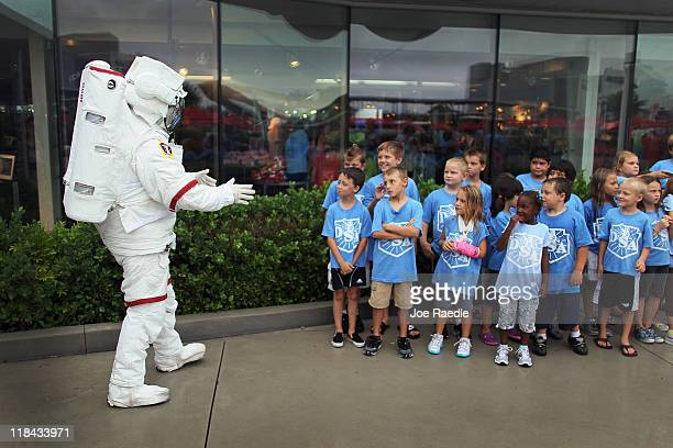 An employee of the Kennedy Space Center Visitor Complex dressed as an astronaut greets children at the center one day before Space shuttle Atlantis...