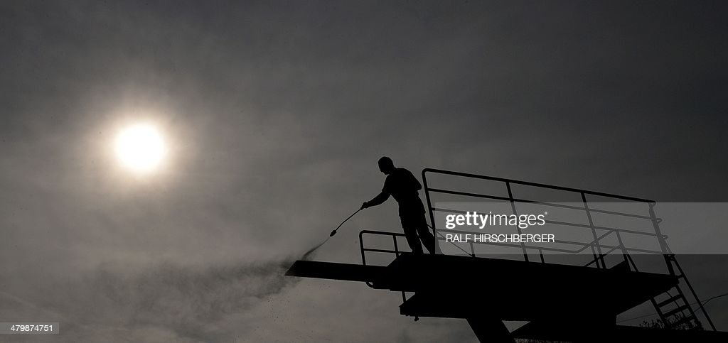 An employee of the Kiebitzberge open air swimming pool cleans the diving platform as preparations are under way for the opening of the season on March 21, 2014 in Kleinmachnow, northeastern Germany. The season is scheduled to start on May 1, 2014.
