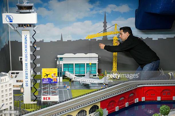 An employee of the Legoland works on a lego bricks model of Berlin's new main airport on January 10 2013 in Berlin Germany is concerned that its...