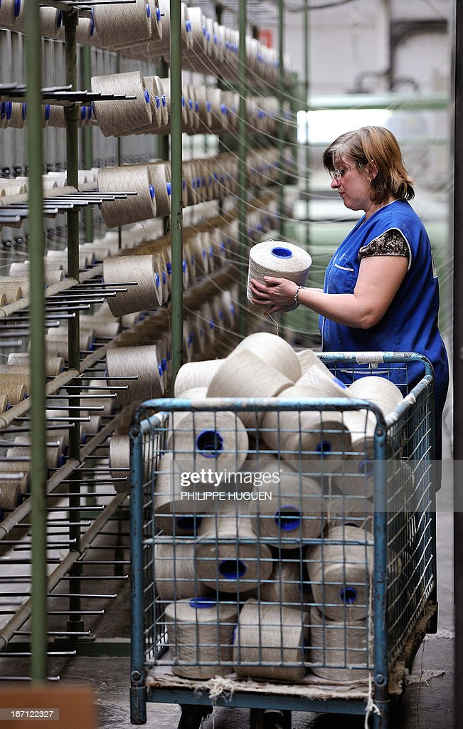 An employee of the Lemaitre Demeestere company installs linen coils on April 16, 2013 in Halluin, northern France.